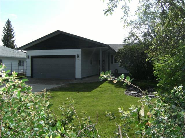 Want to get away from city crowds? Working from home an option? Thinking of checking out small town living? Only 45 minutes to Calgary. A great home  in a great location on Hillside Ave with a great view of the valley!  This move-in-ready bi level with attached garage has a long list of recent updates including shingles, kitchen counter & backsplash, new flooring (vinyl plank & carpet), bathroom updates & new hot water tank plus more. A bright home with main floor laundry, a large living room with wood burning stove, and a fully developed basement with gas fireplace in the family room. A covered rear patio area & storage shed/workshop add to this comfortable home. Quick possession may be possible. You will enjoy this welcoming community.