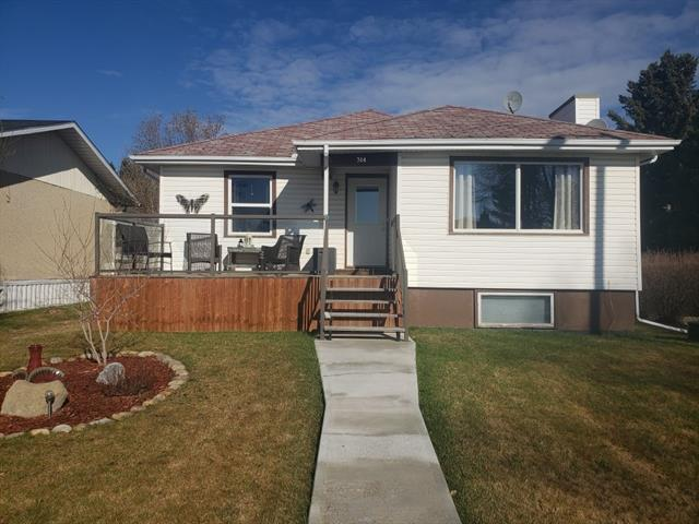 This gem of a property awaits its new owners to appreciate 4 Bedrooms + 2 Bathrooms, UPDATED, OPEN CONCEPT layout. Boasting ALLEY ACCESS on 2 sides, a DOUBLE DETACHED GARAGE, RV PARKING, FENCED YARD, mature TREES, FRUIT GARDEN + a patio to appreciate the west facing yard for its sunshine & shade + coffee with the sunrise on the east facing deck. This BUNGALOW was built in the 50's and has so much charm. In 1995 it was put onto a new foundation. Original HARDWOOD, 2 large Bedrooms, Updated 4 pc bath, WOODBURNING FIREPLACE + a wide open Living Room/Kitchen/Dining area with a COZY FEEL. Newer Hot Water Tank & Furnace along with almost all of the windows have been replaced. Down a few steps is a great porch area leading to the basement where you will love the FAMILY ROOM, 2 more Bedrooms and an awesome 5 PC Bathroom featuring a Double shower & Deep Tub. You will love this Move in Ready Home in this great community.