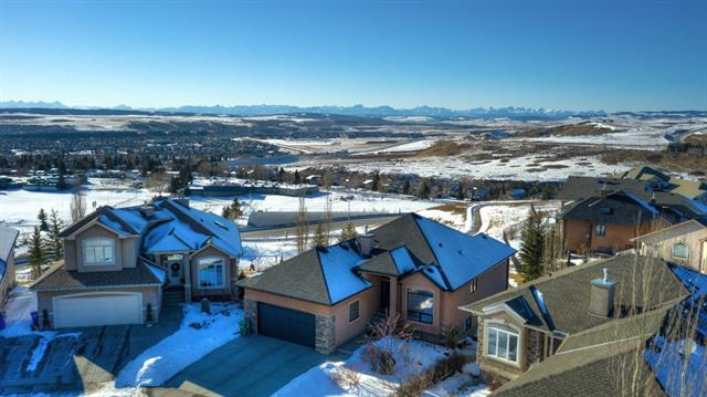 Captivating MOUNTAIN VIEWS. Amazing, Soul Soothing SUNSETS. SPECTACULAR Indoor & Outdoor SPACES. Welcome to 225 Sunterra Views. Step inside ~ as the magnificent VIEWS draw you in to the open great room design with soaring 2-tiered knockdown ceilings w/ painted borders, you'll experience what this beautiful home has to offer: Chef's island kitchen w/ maple cabinets, hi-end appliances including dual fuel range, quartz counters & silgranite sink, transom windows, exquisite trim & millwork, tile & engineered hardwood floors, central A/C, upgraded lighting, Hunter Douglas blinds, and the list goes on. The large master bedrm features a gorgeous 5 pce ensuite & access to the deck w/ extended glass railing. A convenient main flr den, 2 pce bath and laundry rm complete this level. Fully finished w/out basement w/ rvr rock fireplace, media centre , 2 add'l bedrms, full bath & infloor heat! Step out to the patio & take in the breathtaking views! Tucked away on a fenced pie lot in a quiet cul-de-sac. This is THE one!