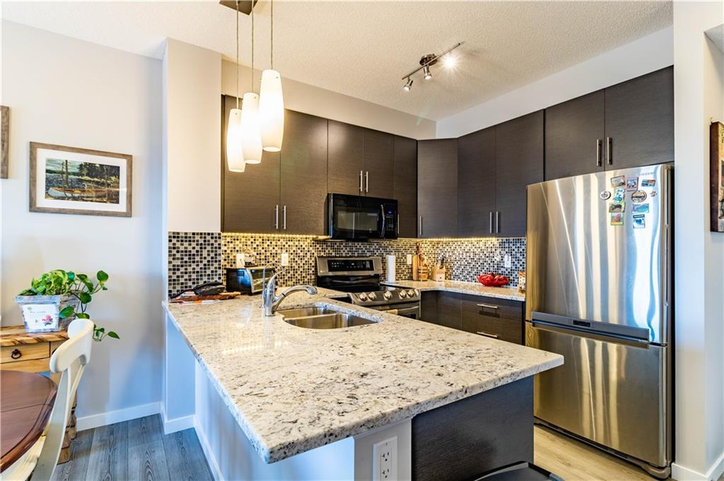 ENJOY GORGEOUS MOUNTAIN VIEWS from this HIGHLY UPGRADED 2 Bedroom, 2 Bathroom Sunset Ridge Condo. Featuring a GROUND LEVEL UNIT with walk-off patio, perfect for seniors or someone with pets. 2 TITLED PARKING STALLS, one underground & one surface stall w/ storage locker, guest suites & gym. This beautiful West Facing unit features 9? ceilings, Granite counter tops in the spacious kitchen w/ black & stainless appliances w/ new stove, living room w/ over-sized windows & access to large patio w/ gas BBQ hook-up & stunning views. Recent upgrades include retractable screen patio door, Hunter Douglas Blinds throughout, custom sliding glass door on master closet, reverse osmosis drinking water system, upgraded shower fixtures & free-standing wardrobe in 2nd bedroom. Master has his/her closets & 3 pce ensuite, with the 2nd bedroom accessing a full bath. 1 dog or 1 cat allowed up to 20 lbs.