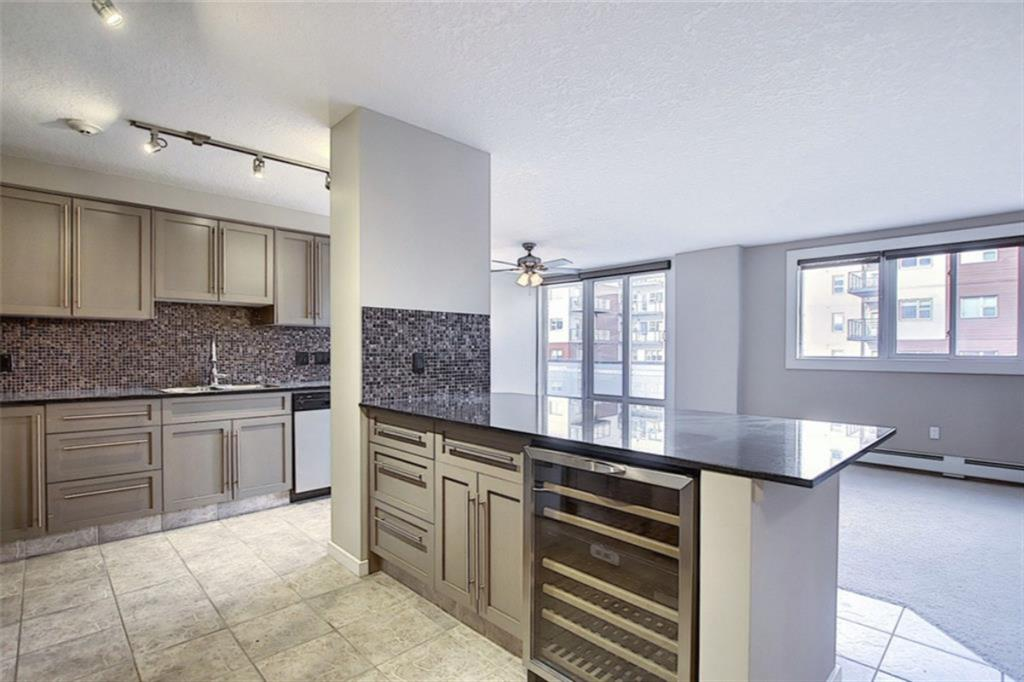 This is your chance to own a huge 2 bedroom apartment with downtown views blocks away from SAIT and the Jubilee auditorium. This unit was originally built as two 1 bedroom condos then opened up into the massive 1,145sf 2bed, 2bath you see today! The maple kitchen cabinets with granite countertops are finished off with stainless steel appliance and gas stove top. The large island comes with a fantastic wine fridge perfect for entertaining while enjoying the city views. The bedrooms are on opposite ends of the suite making it a great fit for a rental or for a home office. The master suite is fit for a king (bed) and the en-suite has a fully tiled shower. In-suite laundry, large closets, massive storage locker and bike room are great bonuses in this Hillhurst condo. The building is nice and quiet due to the concrete construction and also features secure underground parking and gym. Book a showing to see this unit for yourself!