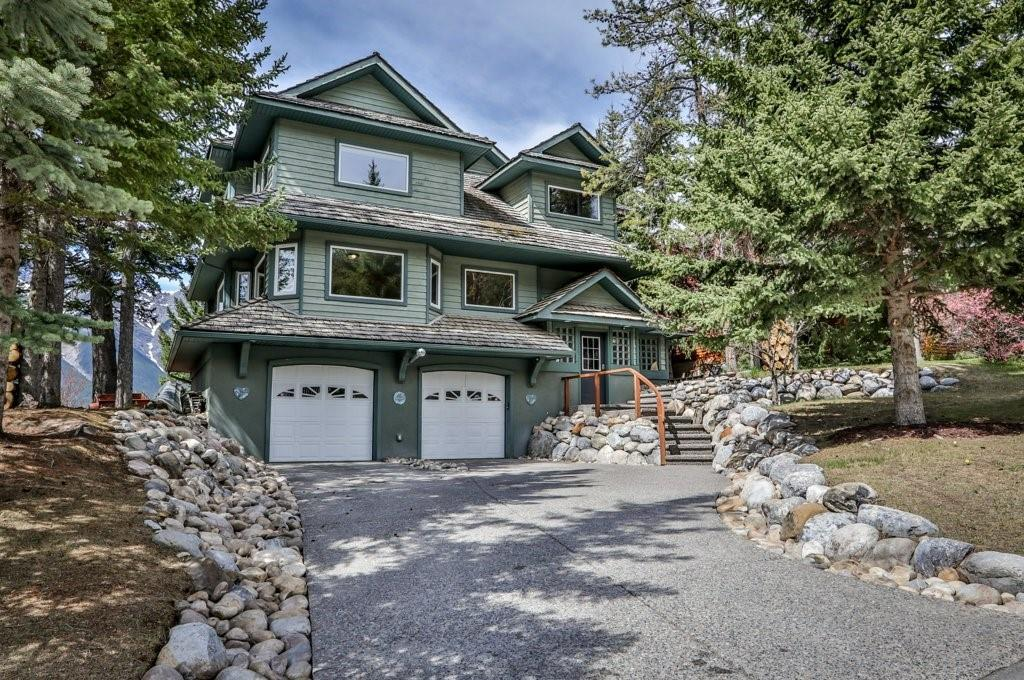 Adjacent to a Municipal Reserve surrounded by trees and walking trails and offering perpetually unobstructed views of the mountains and the Bow Valley, this south facing family home offers ample space for an active family. With four bedrooms, including the master with a five piece ensuite, a main floor office, a spacious flex room suitable for fitness area or TV room, and an open plan living area, this custom built home provides the essentials for mountain living. The great room features a wood burning fireplace and is surrounded by windows capturing views of the Three Sisters, HaLing and the Rundle Range. The oversized heated double garage with additional storage area is also wired for 220v applications, ideal for a woodworking shop. The walk out basement offers a finished bedroom + den with private entrance and the entire level is warmed with inslab heating. Off set from the street & the incredible yard really make this a special & unique property for a family or vacation home.