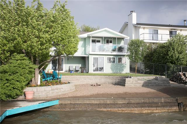 Welcome home to lakeside living. This charming 3 bedroom 2 bathroom lakeside home has it all. This unique property offers the best of both worlds being situated right on Lake Chestermere and close to all the city amenities. The main floor features an open concept floor plan with a large kitchen with solid wood cabinetry, Stainless steel appliances, stone counters and provides breathtaking views of the lake and access to the covered upper patio. The main floor has new flooring throughout and is complete with a large master bedroom, second bedroom and a well-designed main floor bathroom including separate shower, jetted tub and heated floors. Even more extras include all new windows and the luxury of central air-conditioning. The walk-out lower level allows you easy access to your backyard oasis, including campfire pit, several beautiful gardens, private beach and two docks. The lower level is bright and airy and offers in-floor heating throughout the recreational room and large bedroom.