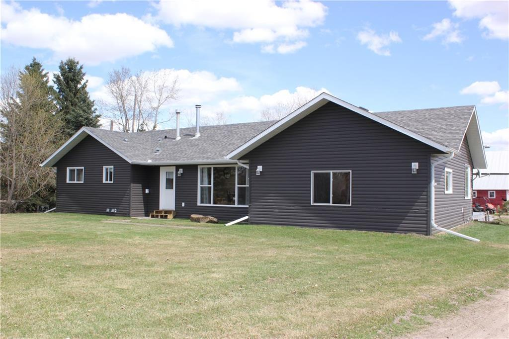 """Fantastic acreage/small farm opportunity north of Olds set up for purebred cattle and could easily converted to equestrian or other livestock on nearly 75 acres of black soil that is productive as any land in Alberta. Located just under 2 miles off pavement and so close to town, schools, & recreation. Warm and inviting 1928 sq.ft, 3 bed, 2 bathroom,""""RANCHER"""" style bungalow on single level is nestled in the trees & protected from wind by the mature shelter belt surrounding the farm yard. Oversized 28x26 insulated-lined double car garage w/ concrete pad out front. Good insulated barn with stalls & steel lined wash rack, open face cattle shelter, corrals, 5 auto waterers, mix of pasture & cultivated, dugout, perimeter & internal x-fencing, surface lease paying approx. $3400 annual. Beautiful lawns and landscaping, well treed yard, fruit trees, & highly productive garden plot. Ready for you & your family, your pets, cattle, horses, sheep or just your own land to to live and breathe"""