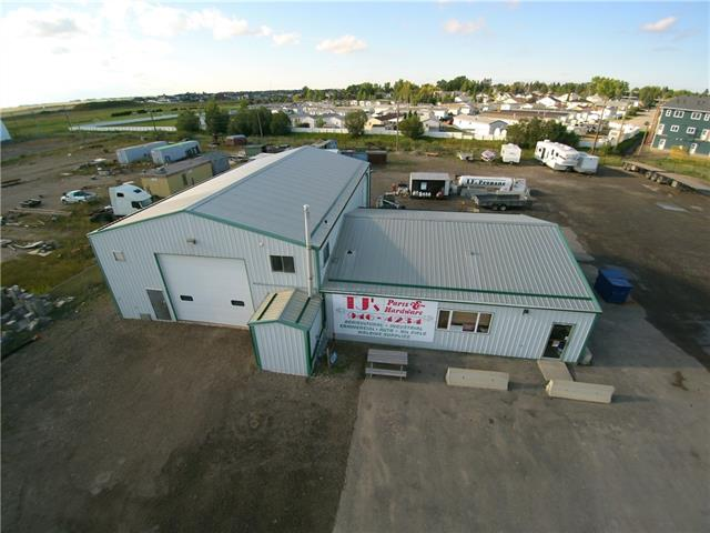 This industrial land is spread over 1.5 acres (with 2 titles), is gravelled, fenced and is complete with an automatic gate. The building offers a showroom, retail space and shop area with 4,165 square feet of space overall with one 3 piece bathroom and one half bathroom.  There are 3 overhead doors (14x16 | 9x8 |12x14) with the office mezzanine measuring 10x16.