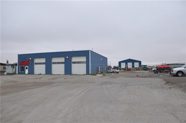 1.4 ACRES with a 4200 SQ FT Steel Structure building.... FEATURES 6 @ 14 ft Overhead doors allows trucks to drive through; office/utility/locker rooms ; originally the building was used as a truck and car wash ; ideal site for a potential second building, subdivision of a second lot [subject to town of High River approval ];fenced yard ; gravel packed rear yard and good highway access.