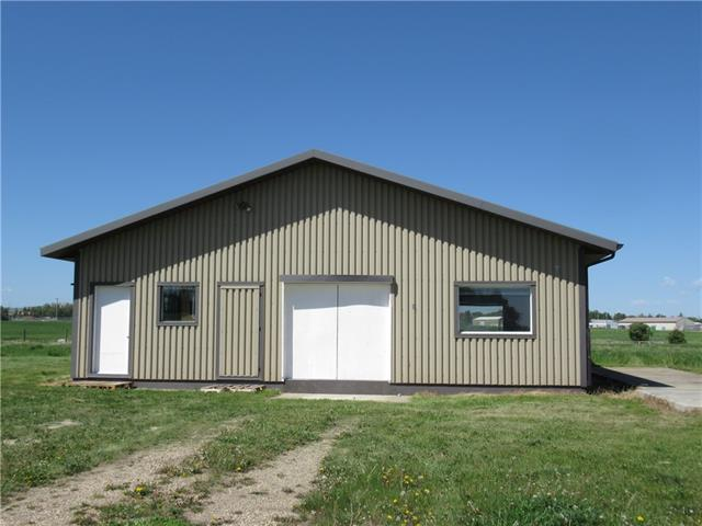 """CALLING TRADESMEN OR MANUFACTURERS looking for your own space for your business endeavors. Excellent building on 1 acre of land adjacent to the Nanton Golf course. 33x39 metal clad building built on heated slab. Former flour mill has had all that equipment removed; 3 phase power in place, with transformer to step down to single phase; disconnect boxes all still there to serve the needs of the next manufacturer. This lot is in the town of Nanton but has no services to the sight; so neither water nor sewer. Current (original) owner have a composting toilet to accommodate workers needs. 4 rooms, foyer (reception), office, mechanical room, large workshop; central vac roughed in. A/C has not been used for years so sold """"as is"""". 8 1/2 foot ceilings R-40 insulation; walls are R-30. Freshly painted walls and floor. 3 man doors, plus 8'x 7.2' door to access main work space. Concrete pads on north side of building were bases for grain bins which have been removed.  EASY TO SHOW AND EARLY POSSESSION POSSIBLE."""