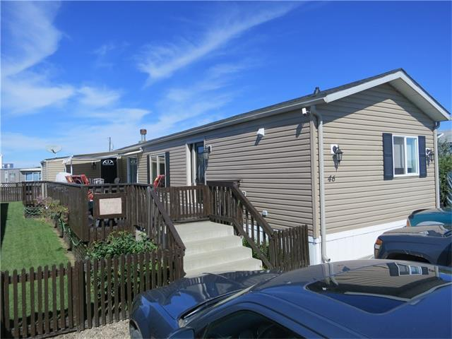 Here is one GOOD LOOKING home in the Carstairs Mobile Home Park! The home has been lovingly maintained and nicely updated. Updates include newer windows and exterior doors (except the porch), window a/c unit, awning over a portion of the huge 39x12 deck, kitchen countertops and most of the flooring. Nice, big living room, lots of counter space and cupboards in the kitchen with a built in desk too. The master bedroom and ensuite are oversized too. At the other end of the home, two smaller bedrooms have been combined to make one but could easily be split up again. Ample parking in front round out this awesome home.