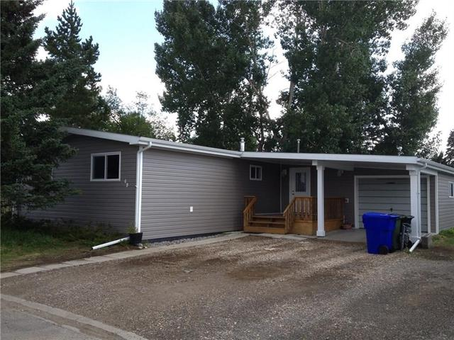 Welcome Home! This open concept double wide mobile home on a rented lot is affordable and perfect for you!  Enjoy the massive eating bar or spent time on the outside deck.  Home is located on a fenced, double lot with mature trees. During the past few years, upgrades include new windows and exterior doors, new roof and shingles, new exterior siding, and new deck (12'x30').  All water lines have been replaced, and bathrooms were upgraded.  Inside, new flooring and paint as well as appliances, wood stove, furnace and hot water tank were all replaced.  Make this your new home!