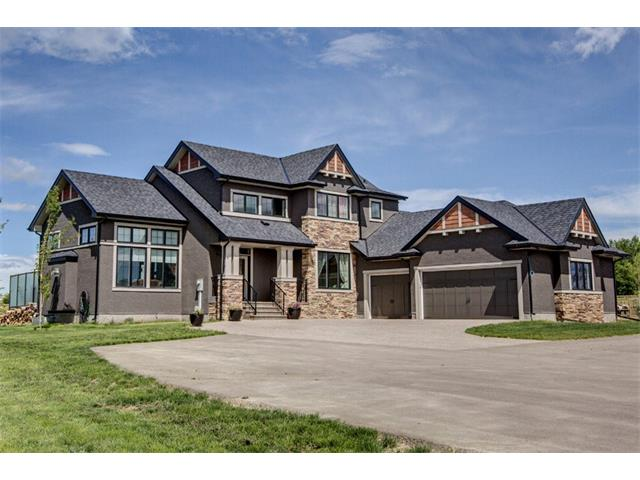 Dreaming about getting out of the City without losing all the amenities?  This fabulous country estate home is just right for you! Just 10 minutes from Calgary & all the amenities - LRT, shopping, theatres & more!  This gorgeous Baywest built home is nested on a treed & landscaped 2-acre lot.  With over 2400 sq. ft. above grade plus over 700 sq. ft. in the fully finished basement, you can have it all.  Beautiful gourmets' kitchen, living room with dramatic stone fireplace, master bedroom retreat with steam shower, games/media room, den & more. With a total of 4 bedrooms, 2.5 baths and a huge heated 6 CAR GARAGE/SHOP this is the perfect home for that growing family. This home features great outdoor living with a large deck, patio with fire pit. There is a great greenhouse for the green thumb in the family. Total acreage is fenced & the driveway is paved. Worried about losing power in a storm, don?t this house has a Natural Gas Generator that will keep the light on and the water running. Call today to view!