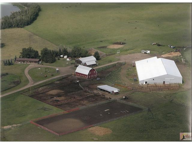 Top Class Equestrian Center just minutes East of Ponoka. 80x200 insulated, heated indoor riding arena with finest quality attached 43 stall heated barn. Wood plank flooring. Upper mezzanine viewing area and office/sitting room. Heated washrooms. Wash rack. Two huge tackrooms. Also as part of the arena complex is the attached hay and shavings area for easy access. the heating system is hot water. Animal handling pens and alley ways make for quick movement of cattle and horses. An 80x150 outdoor sand ring is another feature. The refitted hip roofed Red Barn is a focal point from the road and an added bonus. All on 155 lush acres siding on Nelson Lake. Add a 1548 sq. ft. bungalow with its west facing deck that looks out to the lake and private foal paddocks, and you have the finest Equestrian Estate around. High vaulted ceilings and great rock fireplace are some of the extra features of the home. There is also a shop, equipment storage and additional out buildings to complete the package.