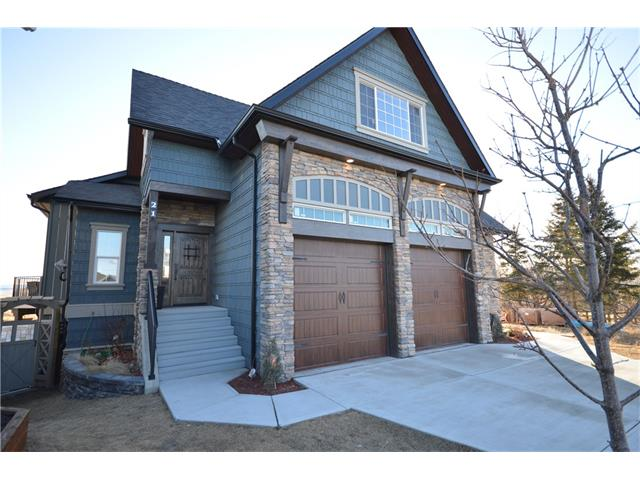 HANDCRAFTED WITH LOVE! This custom built home will have you amazed as soon as you drive up in the quiet cul-de-sac. Heated floors and handcrafted wainscoting welcome you in the main foyer. Expansive ceilings and custom knotty alder cupboards invite you into a kitchen built for a chef. Double builtin ovens, gas stovetop, huge island with quartz countertops, and a walk-in pantry will make entertaining a breeze. Beautiful windows in the main room lead your eye to expansive views of the prairies and the rockies. The massive main floor master bedroom boasts a 5 piece ensuite , with steam shower and jetted tub. The master closet has been designed with the clothes lover at heart! The upper loft area boasts 3 vaulted bedrooms and a bonus room.  The lower WALKOUT level contains 2 more bedrooms a huge living area with gas fireplace and a great living space for the in-laws. Fully landscaped, with additional 3 car parking at rear .There are so many extras to mention. Please see photo comments!Country living in town!