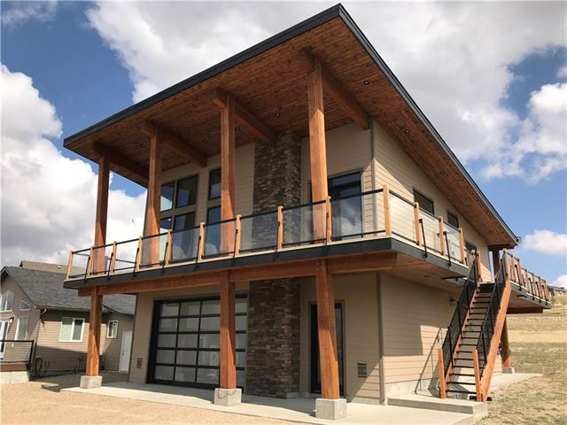 Tired of fighting traffic west & north of the city or on the lake? There?s a better option! Just 90 minutes from Calgary, Little Bow is one of the warmest spots in Alberta.  Enjoy scenic walks where the cactus grows wild and take in the beauty Southern Alberta has to offer. This gorgeous two story home is custom designed and built with over 2195 sq./ft. of living space, 4 bedrooms and 3 bathrooms. The large open concept kitchen/living room has stunning floor to ceiling windows and fireplace, with real timber accents. The oversized double garage can accommodate your ski boat (and tower!) and still have room for your car and other toys. Head outside and a wraparound deck doubles as the perfect spot to relax or entertain on warm summer evenings after enjoying a day of boating and swimming in this deep, clean lake. In the winter you can ice fish, skate, and then warm up by the fireplace! This quiet community and beautiful lake meets all the requirements for a great recreational getaway.  Call today to view!