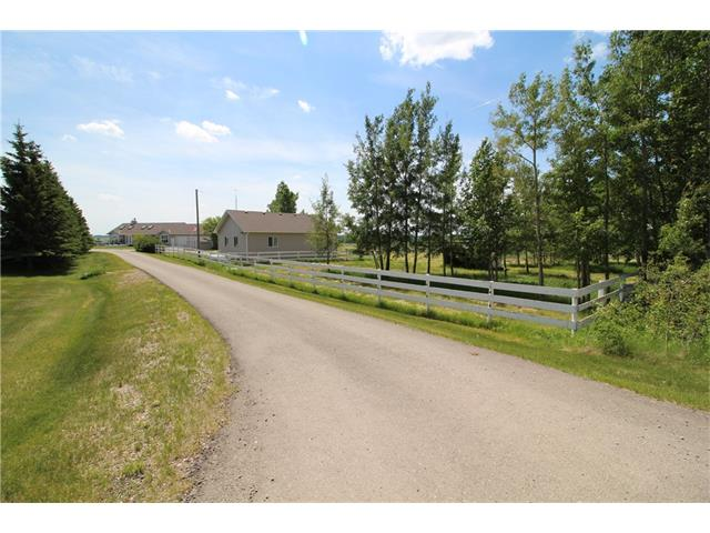 Attention Horse Lovers & Gearheads ? This place is magnificent!  12.31 acres, beautifully set up, incredible mountain view, paved driveway/roads within the fenced and cross-fenced property.  Includes a 28 x 38 heated shop finished with 5/8 tongue & groove and a car lift, paddocks with waterers, a hay shed and 4 storage sheds.  The custom horse barn has tack room, 5 stalls and 2 tie stalls.  In addition to all this, the 1350 sq ft bungalow has lots of huge windows and sky-lights giving it a bright and airy feel.  The main floor boasts hardwood floors, a kitchen with plenty of counter and cabinet space, a dining room, a living room with a striking river-rock fireplace, two bedrooms and two bathrooms.  The master bedroom has two closets and a huge ensuite.  Laundry areas on both levels.  The lower level is a fully-finished walk-out basement featuring a one-bedroom suite.  A triple-car garage is also attached. Quick commute to Airdrie and Calgary.  Don?t miss this great opportunity. Call today.