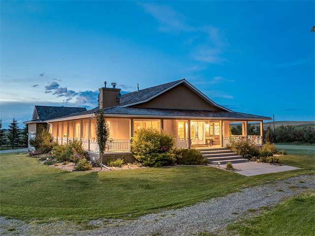 Rare opportunity!Great location. 45 min. to DT Calgary, 30 min.to YYC,10 min.to Cochrane. Upgraded bungalow that has the privacy, mountain views and mature landscaping you've been dreaming of. Set well back from the road, enjoy country living at its finest with a 5 bedroom, 2200 sq ft renovated rancher. Enter into a soaring open space with dramatic vaulted ceilings, hardwood floors, chef's kitchen and 3 bedrooms on the main level, including a large master suite with new spa bathroom. Huge rec room and 2 massive bedrooms, bathroom, bar and gas fireplace on the lower level. Over 1000 ft of deck space including a covered wrap-around veranda and an entertainment deck w/hot tub out back. Two 30x50 Quonsets, one set up as a shop w/gas heater, water and power and the other as a barn w/tack room & wood box stalls. Excellent round pen and outdoor riding ring under construction, green house with attached equipment shed. There is a serviced trailer pad in the yard w/power,water and septic tank. Don't miss it!