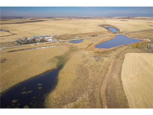 15.99 Acres w/ water access & $3900 annual income from Encana Gas well. Looking for a special piece of property w/ great development potential, you have found it. This special piece of property is 16 acres & is in an AMAZING LOCATION ½ a mile off Highway #1, ¼ mile off Highway 561 & 3 minutes to the NEW k-12 Wheatland Crossing SCHOOL! Gates from the canal allow water to stay or go from the land. Looking to INVEST, hold on & reap the benefits later, build your DREAM HOUSE on an amazing piece of land or need a great piece of land for COMMERCIAL development that requires water, this is it!! Zoned AG which can allow AG Operations, Nursery, Greenhouse, Bed and Breakfast, Modular home, Kennel, home business + Gorgeous views of a protected Ducks Unlimited pond, the rolling FOOTHILLS & MOUNTAINS & only 10 minutes from Strathmore and 35 minutes from Calgary. Services to property line including 3 PHASE POWER. Can be sold with adjoining 16 acres & 60 acres piece. OFFERS WELCOME!