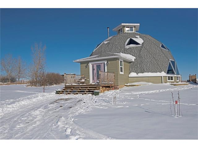The word ?unique? is over-used but it is entirely apt here for this beautiful, 2,700+ sf, custom built Dome Home, set on 4 quiet & fenced acres, just a few minutes SW of Okotoks. Structurally super strong, incredibly well insulated, fabulous family oriented floor plan - you will definitely want to TOUR THIS HOME IN 3D (Click on the Multimedia/Virtual Tour Button) - to learn more. Brief features include a stunning, open to above, living room with a wood burning fireplace, a sumptuous main floor master bedroom with a 5 pc en-suite & access to a huge rear deck, a wonderful kitchen/dining area, two large upper level bedrooms, one with a 2 pc en-suite & both with their own mezzanine level and the quite fantastic cupola, offering panoramic mountain and Foothills views. Add in an over-sized detached garage with a workshop at its rear & you have a superb living solution. You will absolutely want to add this home to your list of acreages to see. You will not be disappointed!