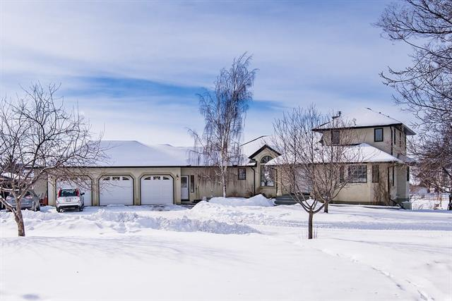 ~~SUPERBLY RENOVATED walk-out home with over 4300 sq.ft of developed space located minutes SW of Calgary on 10.7 acres of land.Step into the spacious foyer opening into the Great room and WONDERFUL DREAM KITCHEN boasting White cabinetry, huge island, GRANITE countertops, UPSCALE appliances and loaded with windows for natural lighting. You will be amazed at the warm, inviting great room featuring soaring ceilings,gas fireplace and feature built-in bookcases.Total of 6 bedrooms and 5 full baths and 2 half baths make this an ideal home for the large family or extended family with the MASTER BEDROOM complete with spa-like ensuite located on the main floor.The lower walk-out level is very bright and offers a country kitchen that can double as a bar area.Furnaces have been upgraded and the shingles on the roof were replaced in 2013.Unique outside bar-b-que area for family gatherings. BEAUTIFULLY landscaped around the home with mature trees and outbuildings are ideal for storage.