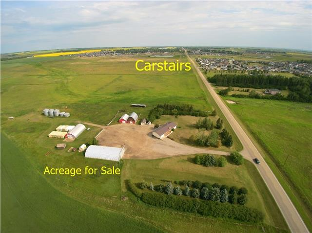Great location. 30 acres bordering Town of Carstairs. Paved road easy access to highway 32 x 54 shop with cement floor,39 x 82 Quonset,26 x 32 barn with hay loft, 24 x 32 shop,12 x 16 shed and a 12 x 24 garage. 1500 sq.ft. home with 3 bedrooms on the main floor and 3 bedrooms in the developed basement also has 3 piece bath and family room Many possibilities for development or using the site for commercial use. Adjoining 1/4s also available