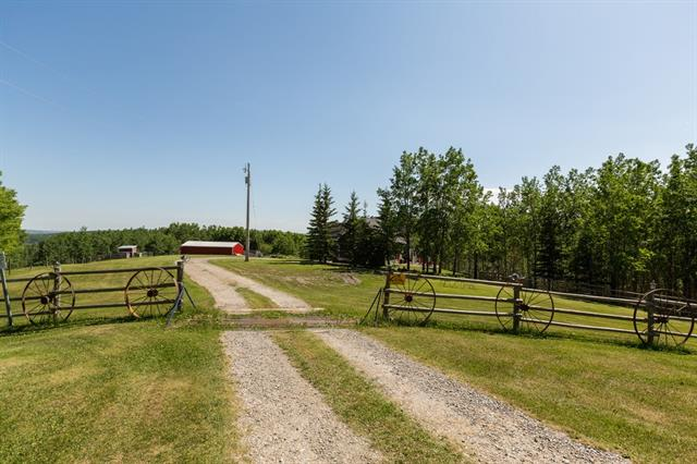 This property is pretty in all seasons & has a nice mix of trees & pasture. If you are looking for a private location on a large piece of land this is a must view. It is located only 30 minutes to South Calgary & an easy drive on well maintained roads. The unique home has the master bedroom & ensuite conveniently located on the main floor. The living room has a wood burning fireplace & opens up to the formal dining area. The kitchen has been updated & as with all rooms, there are gorgeous views from all windows. A home office is privately tucked away at the back of the home. There are 2 more guest bathrooms at the front & back of the home. Up stairs you will find a kids retreat with 2 generous bedrooms, a full bath & a clever playroom. The walk out basement is fully developed with a huge laundry room, full bathroom, great room, exercise area & bedroom with a wardrobe. The barn is set up for horses or toys & the area is surrounded by large parcels of land & natural reserves. This is a wonderful lifestyle.