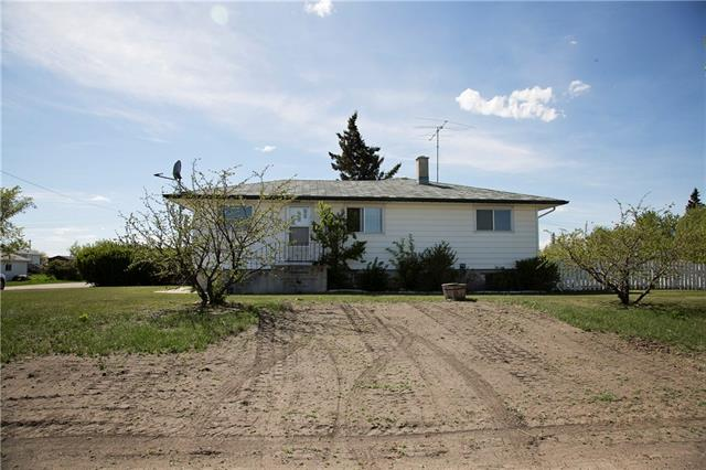 Need room for a big garage or lots of room for kids and dogs to run?  This bungalow is located on an oversized,  lot (approx 100'x100') in Carseland and looks over a prairie field!   Features incl 2+3 bdrms & 2 full baths.  Freshly painted, the main floor boasts original hardwood & incl a spacious living room, kitchen with island, 2 bdrms & a full bath.   The lower level features a family room, 3 bdrms & a 3 piece bath.   One of the bdrms has direct access to the bath, making it perfect as a lower master bedroom with ensuite.  The yard is fully fenced & has fruit trees incl sour cherry, plum, apple & pear.  A newer deck has a hot tub that is sold AS/IS. The home includes a single detached garage & lots of room for extra parking.  Front yard will be re-seeded.  Carseland is a 25 minute commute to Calgary & is a short drive to the Bow River and Wyndham Park; perfect for weekend hikes, fishing and bird watching along the Bow.    Discover the joys of small town living!   PLEASE ALLOW 24 HOURS NOTICE TO SHOW.