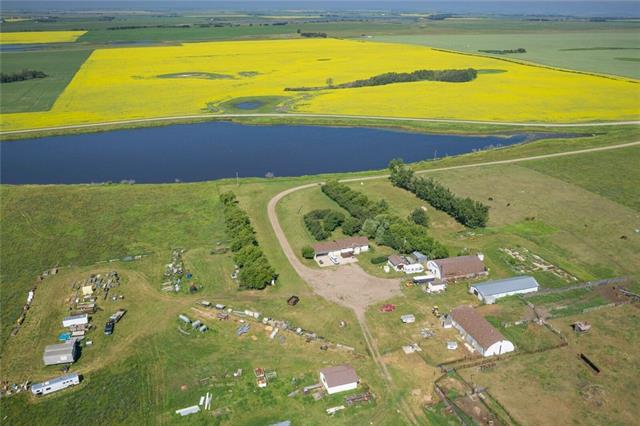 144.93 ACRES OF AMAZING FARM & PASTURE land w/ INCOME POTENTIAL & $3300/year gas well income! BEAUTIFUL POND & HORSE set up including Barn, watering bowls, fencing, gates, panels + MORE! The house has a NEW roof & offers 4 bedrooms, 2 RENOVATED baths, updated kitchen w/white cabinets, black appl. package, tile backslash +NEW pressure tank & developed WALK UP basement w/Summer kitchen! Tons of out buildings incl. ATTACHED double garage w/NEW door & HEATED workshop area, 71*32 shop, 58*38 shop, 77*23 Barn, detached garage + 4 additional sheds! The yard is PRIVATE & offers a garden area, Mature trees, fencing & views of your BEAUTIFUL front POND! This property is perfect for a livestock operation w/ dugout & over 110 acres fenced & cross fenced! It offers a 4 acre home site, 30 acres native land, 80 acres of hay or pasture & 30 acres cultivated! Only 1 mile to the highway, yellow school bus service, under 15 minutes to Strathmore & quick access to Calgary & Cross Iron Mills! Further sub division potential!