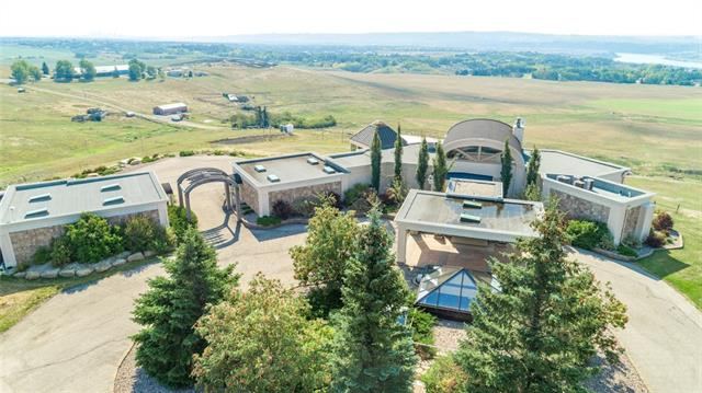 Perched on a rolling hillside lies this exceptional 20 acre luxury estate like no other. Offering unobstructed panoramic views of downtown, the river valley & Rocky Mountains, with oversized 2+3 car garage(s), & massive arena ready for equestrian or sports interests, a very special quality of life awaits the new owners. This highly valuable sub-dividable lot near city & schools creates substantial enduring value. The long private drive leads to a focal landscaped courtyard where a pyramid of glass in the center of the carport greet you. The portico entrance welcomes & flows into the dramatic open living room with stunning barrel vault ceiling & full height windows. A chefs kitchen offers an immense island suitable for grand entertaining & meal preparation, while breakfasts can be enjoyed in the stunning sunroom nook year-round. The open living room offers relaxed comfort with a beautiful fireplace & features a gorgeous hideaway loft library for quiet reflection.   Please see Additional Public Remarks...
