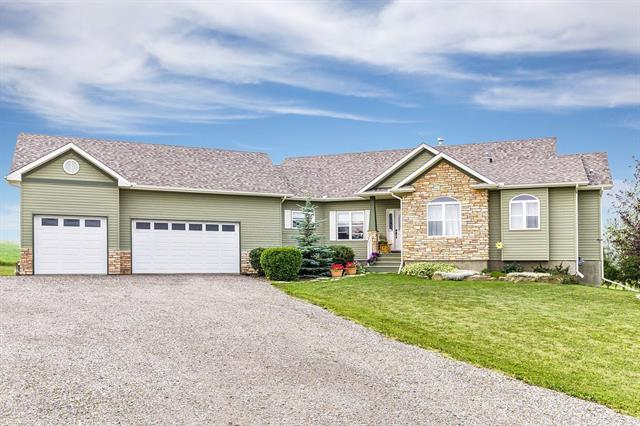Fantastic location close to popular Strathcona-Tweedsmuir school, and less than 10 minutes to Calgary on all paved roads. SUPERBLY MAINTAINED walk-out bungalow with over 3100 sq. ft. of developed space on 4.3 acres. Spacious entryway leads into the great room/formal dining/kitchen combination featuring HAND SCRAPED MAPLE HARDWOOD FLOORING. Wonderful open plan with vaulted ceiling and stone-faced gas fireplace in the greatroom. STYLISH KITCHEN BOASTS WHITE CABINETRY, granite countertops, breakfast bar area and huge eating area loaded with windows. Master suite offers unique tray ceiling, walk-in closet and 'SPA-LIKE' ensuite with 'stand-alone' tub, huge shower plus his/hers sinks. Second bedroom up is currently utilized as a den with huge picture window. Warm,inviting lower level boasts good-sized rec room which walks out to the back of the home. There are 3 additional bedrooms plus jack-and-jill bath plus additional bath with huge walk-in shower. SUPERBLY LANDSCAPED with pond and trees.