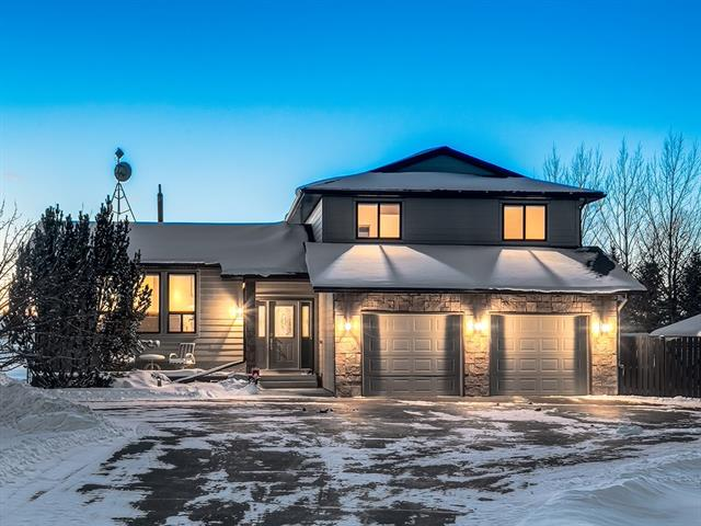 WELCOME to a PARADISE ACREAGE just 10 mins from CALGARY!!! PLENTY of CURB APPEAL, MATURE Trees, TONS of INDOOR PARKING (2 O-Sized Doubles!) + OVER 3341 sq ft of UPDATED, DEVELOPED LIVING SPACE on a 3.96 ACRE LOT w/GENERATOR! WELCOMING Entrance, Living rm w/GORGEOUS h/w floors, BRIGHT Dining rm, Kitchen w/MATCHING S.S. appl, GRANITE counter tops + GRANITE B/S, Windows over sink, B-fast nook w/MORE GRANITE, LARGE Family rm w/STUNNING Stone FP + DECK ACCESS, Mud rm w/Door to HOT TUB/POOL AREA, Laundry rm + 2 pc bath. Upstairs w/MORE HARDWOOD, 3 pc UPDATED Main Bath w/GRANITE counter tops + O-SIZED SHWR, + 3 Bdrm's incl HUGE Master w/SITTING AREA, PRIVATE BALCONY, W.I.C + LOVELY 3 pc EN-SUITE. Bsmt w/BIG 4th Bdrm, 3 pc Bath, GIANT Rec rm w/FP Insert + GENEROUS Storage rm. B-yard w/EXTENSIVE deck incl. Privacy screens, COVERED Hot tub + in-deck POOL, MORE Deck space outside Family rm/Kitchen + ALL THE BACKYARD SPACE YOU COULD WANT!!! LARGE fenced portion + MORE BEYOND! COUNTRY LIVING CLOSE TO THE CITY!!! WOW!