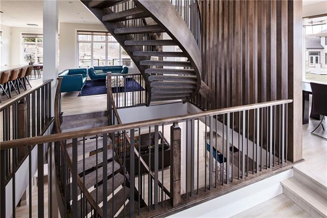 Builders own home for quick possession.  This 5/6 bedroom has a spectacular entrance with criss crossing open riser curved staircases and a paneled cling.  To the right of the foyer is a bright and sunny dining area on the front with an office or kids play room behind it with patio doors to a covered deck and double sided contemporary fireplace.  Beyond the staircase from the foyer is the living room with a spectacular full width tile fireplace.  The kitchen with full height cabinets features a SUBZERO, WOLF INDUCTION COOKTOP and WALL OVEN.  A cast iron farm style sink sits in a large island with a luxurious deep granite edge.  The sunny eating area leads to the covered deck with cedar soffit, two 220 volt rough ins for heaters and two gas lines.  A cooks pantry with pan racks and tons of storage leads to the mud room with shoe racks, locker style coat storage and yes a costco cupboard. Tucked away by the 2 piece bath is a coat room.  The 3 car heated garage also has  SEE COMMENTS