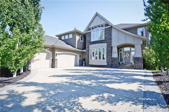 """Please click """"Multimedia"""" for 3D tour. Heritage Pointe at The Lake Perfection! Rarely do homes on this street/this side of the street come up for sale! Amazing fully finished, 2 storey W/O, with very large lot backing SOUTH onto a natural ravine! Fabulous features include: huge chef's kitchen with 2 sinks & 2 wall ovens, gazebo with hot tub, movie room with 133"""" screen/theater seats/7.1 surround sound, wet bar, oversized/heated triple garage with attic/storage space, fully finished walkout basement, massive lot with mature trees - almost a 1/2 acre, gym, U/G sprinklers, over 5100 sq ft developed, RO water conditioner, 3+1 bedrooms AND upper hobby room could easily be a 5th bedroom, 10 ft ceilings on main, excellent floor plan & much more! Location is outstanding - park/green space DIRECTLY across the street, backing onto an expansive/private ravine & minutes to south Calgary! Year round lake/beach amenities, buses for all schools - what more could you ask for! Move in ready and total pride in ownership!"""
