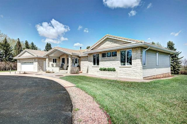 Beautiful family home on 23 acre oasis. On pavement only 4km east of Airdrie city limits! Over 4500 sf of living space, this immaculate bungalow has everything you need to raise a family. A yard like no other - stunning landscaping & irrigation, paved driveway, interlocking decorative paving stones, back & front patio, fire pit, play-set, trampoline, playcenter w/tree house, climbing wall & zip line, 50x14 greenhouse & 24x30 workshop. A large foyer welcomes you & leads to a large gourmet kitchen w/ double ovens, loads of storage, corian counter tops, breakfast nook & desk. Formal dining rm & sunken living rm w/ bay windows awaits your guests. 2 bedrms w/ walk in closets & 1 w/ an ensuite. Master retreat is huge - featuring a beautiful walk in closet & 5 pc ensuite. Laundry rm w/ wash up sink & office/bedroom complete the main flr. In-floor heating thru out. Fully finished basement features a rec rm, 2nd office, fitness rm, playroom and loads of storage space. Remodeled in 2001 & has nice upgrades!