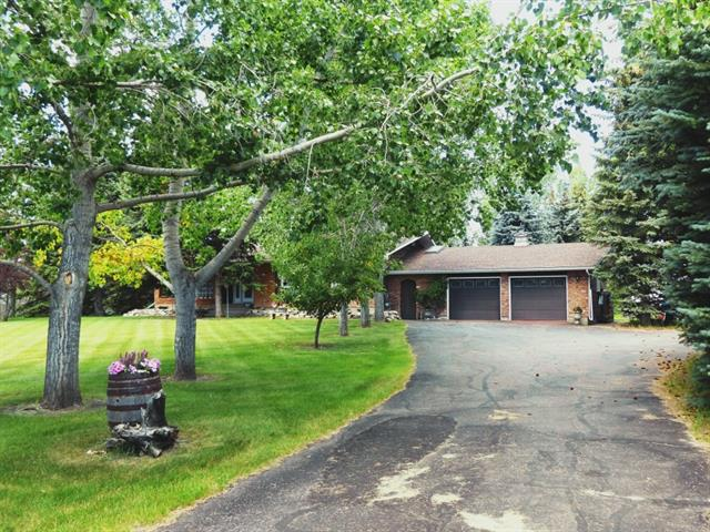 "Owner is open to you selling your home first. DREAM acreage! Trees: around 200 mature spruce and poplars, feels like your own private forest. On 4.5 acres, minutes south of the city limits. First impression of the house is how spacious and bright it is. Bungalow, almost 2900 sqft, well taken care of. A unique plan that fits a country lifestyle with an abundance of windows that really brings the outside inside. Country living kitchen with island that overlooks your own lily pond and waterfall. Big family room with fireplace, dining room/living room combo. Nook leads to a newer 720 sqft 2x6 cedar deck, shielded by 50 foot tall spruce and a great view of the pond. Awesome master with large 6 piece ensuite and an enormous walk-in closet. M/F also features a den, guest bedroom and 2.5 total baths. Lots of closet space. Your back entrance/laundry room is perfect for boots and a ""drop"" area. Acreage could accommodate some horses with a older barn, horse shelter and water in place. Extra Detached garage as well."