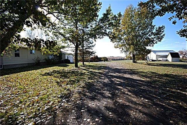 17.21 Acres with Municipal Water and drilled well,  2018 Septic Tank and Field. Great acreage just West of Linden featuring a spacious 4 bedroom raised bungalow with mature trees and park sized play area for the kids. Over 1600 sq. ft. on the main floor, large front entrance, bright kitchen, separate dining room, over-sized living room with large windows and private sitting area next to the back deck patio door. Comfortable master with 3 piece ensuite and another 4 pce bath on the main level. Lower level features a large family room, office/den and a 2 pce bath. 16' x 24' garage and a 24' x 28' shop for all your projects.  The County of Kneehill allottment for animals is one head per acre, so you can certainly have lots of horses or whatever you wish.  House could use some updating but is certainly ready to be moved in.  Great location with good access to Old, Airdrie, Red Deer and Calgary.