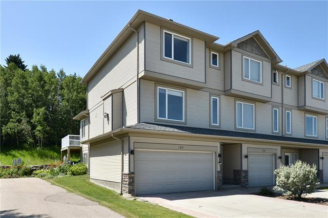 Here is your chance to live in desirable Crawford Ranch. This fully finished end unit with double garage is a bright and open 3 storey backing onto a peaceful treed area. A large bedroom with double close (RI laundry in one), a 4pc  Jack & Jill bath & storage room are on the entry level. Upstairs to the main living area consisting of a living room w/gas fireplace, kitchen w/island & breakfast bar, corner pantry, open to a family room, 2pc bathroom & dining area with access to the deck and view of the trees. The upper level has the Master bedroom w/3pc ensuite, a very spacious second bedroom, 3pc bath & convenient laundry room. This quiet location is close to the Bow River & Jumping Pound Creek with the pathway system just steps away.
