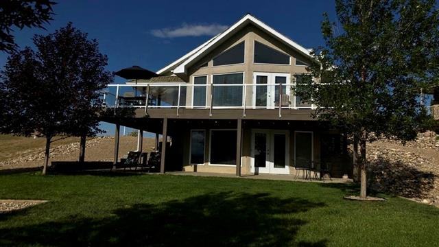 ENJOY THIS LAKE VIEW FROM THIS 1076 SQ FOOT WALK OUT BUNGALOW FEATURING 5 BEDROOMS, 2 FULL BATHS. THIS LAKE IS 130 FEET AT ITS DEEPEST AND IS 17 KILOMETERS LONG AND 10 KILOMETERS AT ITS WIDEST FEED BY THE LITTLE BOW RIVER .. SPACIOUS LIVING ROOM FEATUREING VAULTED CEILING AND LARGE WINDOWS,  WHERE YOU CAN  ENJOY THE WARM EVENINGS WITH FAMILY AND FRIENDS  AS YOU ENTER A WRAP AROUND DECK WITH  180 DEGREE VIEWS TO THE SOUTH WEST  THIS LOWER WALK OUT LEVEL INCLUDES 2 BEDROOMS, FULL BATH, GAMES ROOM WHERE YOU CAN WALK OUT TO THIS FULLY LANDSCAPED PRIVATE LOT ...ENJOY BOATING, FISHING ,AND A SANDY BEACH LITTLE BOW IS LOCATED SOUTH OF THE TOWN OF VULCAN ON HIGHWAY 23 FOR 17.8 KM TURN EAST ON HIGHWAY 529  FOR 27.8 KM, TURN SOUTH ON RANGE ROAD 212 AND PROCEED INTO RESORT ( apprx 3 km         ( please note you will go past little bow provincial park)