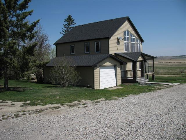 250k below replacement value!! Are you dreaming of living in the country in a beautiful home with land (4 acres) and a view? This property is 1 minute past the Reunion subdivision and has been annexed into the City of Airdrie, meaning there may be future development potential. The main floor has teak hardwood floors, granite counters, stainless steel appliances and a layout to die for! The living room has a beautiful built in with a fireplace and walks out onto the huge deck with a view. The main floor also has a convenient den. Upstairs has the master bedroom, 2 additional bedrooms and a den off the Master. The Master has floor to ceiling windows, a large soaker tub and an impressive steam shower in the en suite. The basement has another 2 large bedrooms and 2 living areas with walk out. There is a single garage, a large shop, and 2 barns. Too many upgrades to list! Call today for more details or to view this spectacular property.