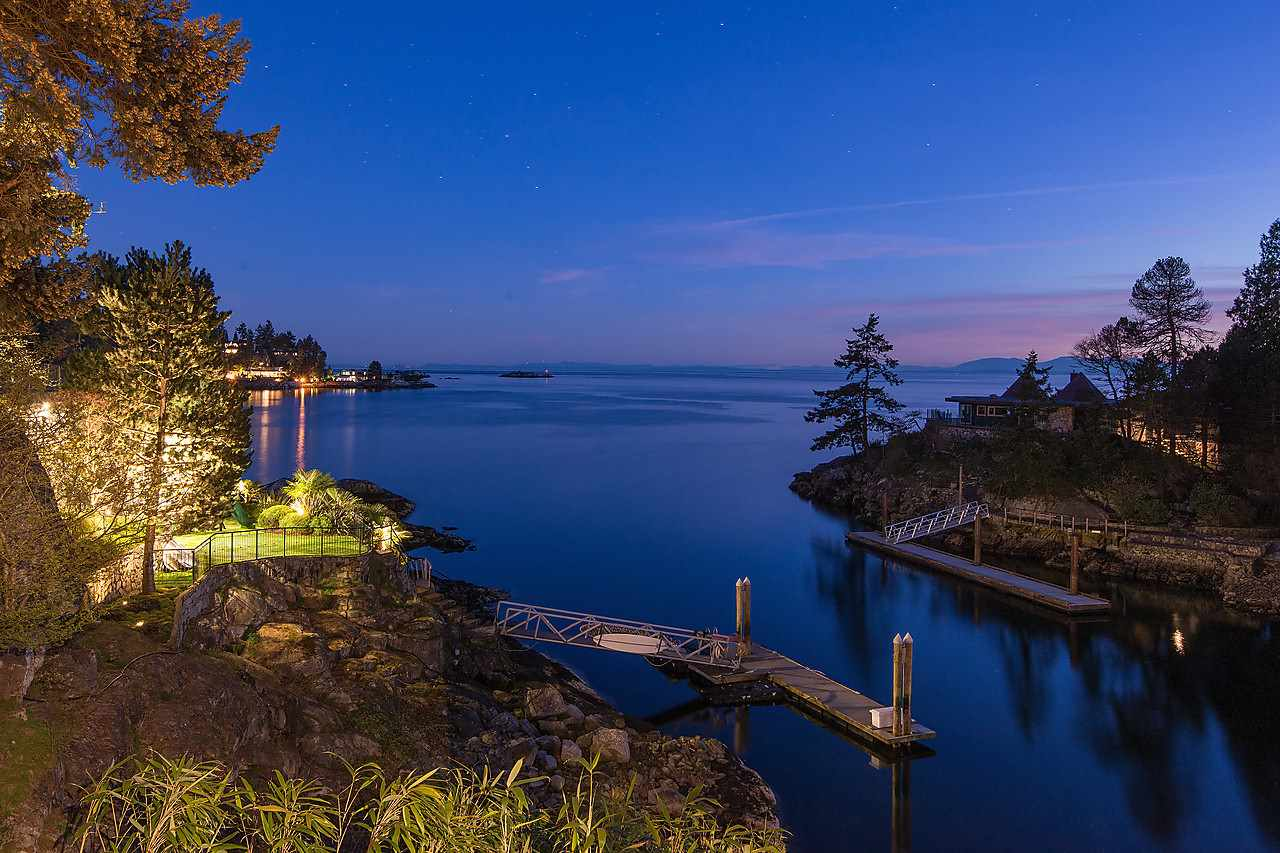 Stunning West Coast contemporary waterfront home sitting on a private 21,000 sq.ft. lot down a private winding driveway with 190 feet of ocean frontage and a 50 ft. deep water private dock.  The views are absolutely spectacular from this wonderful John Kay designed architectural home featuring a fabulous open plan with soaring 24 ft. ceilings, cedar timber columns, beautiful natural materials, a world class wine cellar and separate guest accommodation.  This spectacular waterfront home with its private dock offers a very exclusive opportunity to park your boat in front of your home.