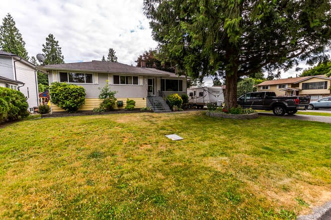 This well kept traditional 1950's home is located on a large corner lot in a quiet neighbourhood-next to Fox Street Park-yet centrally located to all amenities, including Coquitlam Centre and the new Evergreen Skytrain. The main floor offers 3 good sized bedrooms, a large eat-in kitchen with an entertainment sized deck and a separate formal dining/living room with a gas burning fireplace. Downstairs is a cozy family room with a wood burning fireplace, a 2.5 piece bath, another bedroom, a large unfinished space and a separate entrance, allowing for secondary suite potential. This property may also qualify for the construction of a laneway home. Live in, rent out and hold, re-develop...there are plenty of options here!