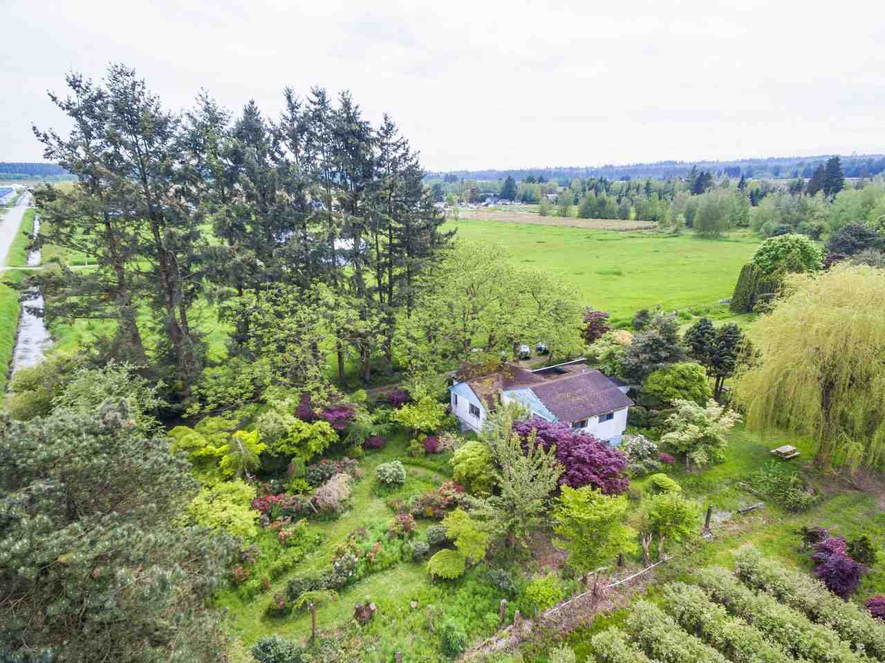 Beautiful, peaceful 4.8 acre country estate property in Pitt Meadows. Design & build your own large estate dream home (potentially up to 10,000 SF). Gated property has a private garden of flowering cherry blossom trees, mature walnut trees, pine trees & graceful weeping willow tree; ornamental & flowering plants such as Japanese maples, rhododendrons, azaleas & peonies. 2.5 acres of mature blueberry bushes on the property can generate revenue. Situated by a quiet road. View of the surrounding mountains. Conveniently located, 5 to 10 minutes driving distance to schools, shopping & restaurants. Demolish existing old house to create your own private estate on this beautiful scenic countryside property.