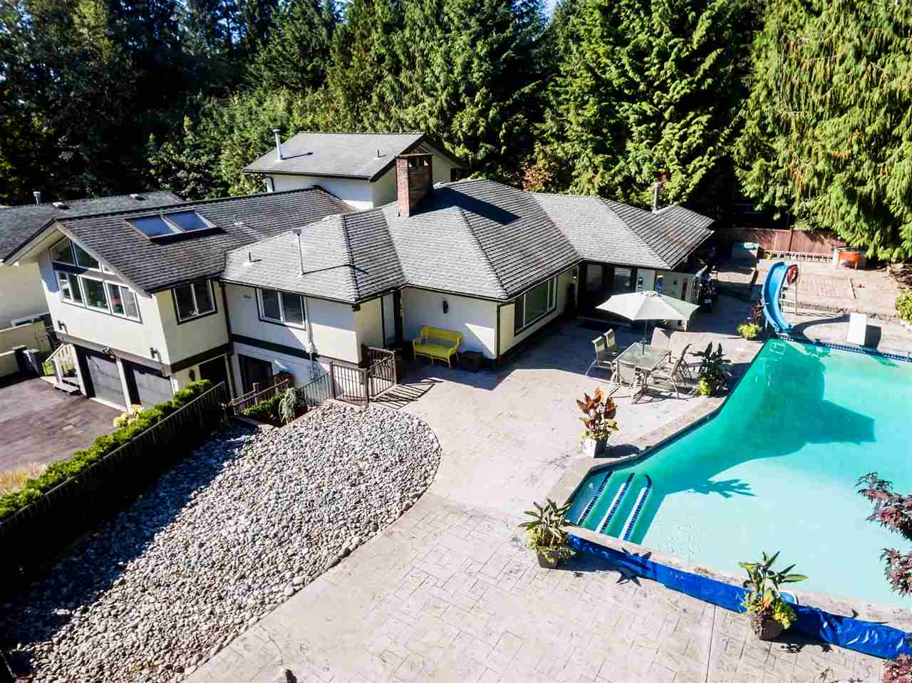 The Perfect Home for Entertaining! Situated in Upper Lynn Valley, this 4,426 sq ft home features 3 bdrms (2 Master Bdrm Suites plus a loft style 3rd bdrm) & 3 full baths up. The lower level has a fully registered Suite w/a large newly renovated Kitchen, large Living Rm w/FP, a Dining Rm, 2 Bdrms & a 4 pc Bath. The lot is 13, 328 sq ft & includes a gorgeous concrete pool surrounded by a stamped concrete patio (features a direct gas bib for a BBQ, a direct gas Fire Pit, & a Pool house (which includes a 3 pc Bath). The Kitchen was designed by a caterer for a caterer featuring dble wall ovens, Jenn Air cook top, wine fridge, trash compactor, garburator, double sink plus a prep sink, lots of granite counter space, heated floors plus lots of windows & well-appointed skylights to take in the mountain views while you cook/entertain. The open plan main floor flows seamlessly from large Living rm to generous Dining rm & finally huge Family rm; the perfect combination for family gatherings/entertaining. A must see!