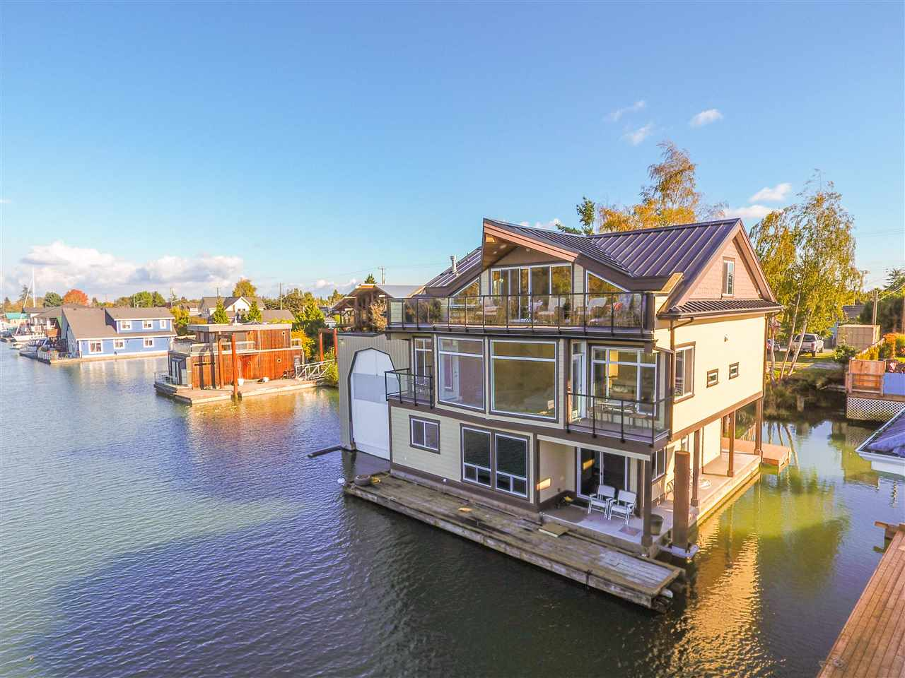 Spectacular waterfront residence just steps to Historic Ladner Village! Set on the banks of the majestic Fraser River, this custom 2016 home offers breathtaking panoramic views, stunning appointments throughout & a private attached boathouse allowing you to moor a 34'+ yacht. This unique property includes a 5,200+ sqft lot w water rights & a 3 bedroom plus loft, 4 bathroom home w over 3,100 sqft of living space. An open concept main level takes advantage of the views w large windows & you will love the gourmet Miele chef's kitchen w oversized island & stone counters. Other highlights incl wide plank wood floors, privacy glass & motorized blinds & luxurious master w dream ensuite. Bonus: opportunity to build a second house on the property & detached 3 car garage. Inquire for more details!