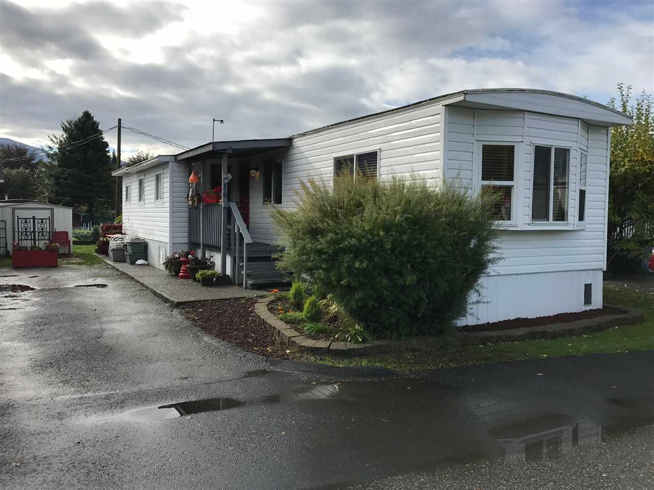 """Gently live in 2 (possibly 3) bedroom mobile home in nice, tidy park in a """"walk to everything"""" central Agassiz location. This home is clean, has a nice open + spacious main living area, and has received some modern touches. White kitchen cabinets have been refaced, and some windows have been upgraded. Plenty of storage in the added utility/storage rooms. Enjoy your morning coffee and Mt. Cheam views from your covered front porch. A little added privacy with the large green space behind, and there's two garden beds for the outdoor enthusiast. Exterior storage shed too. Pad rent will be $520.00 & includes garbage, sewer, street lighting, & snow removal. An affordable opportunity in Agassiz."""