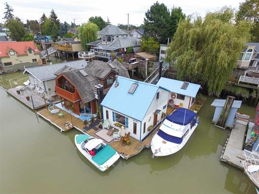 LIVE ON THE WATER AND OWN PROPERTY TOO! Fabulous location close to town centre, walking paths, dyke, parks & farms.  This unusual property offers the described float home and two boat slips (no moorage to pay)as well as a half share in a rental property, on the land.  The float home has one bedroom in the main house and a guest bed/office/laundry in a smaller home.  The views from the home and the deck are fantastic with beautiful sunsets, swans, eagles and other wildlife. There is extra storage and a work shop.  This is a rare opportunity to live on the water and have FREE moorage for 2 boats.