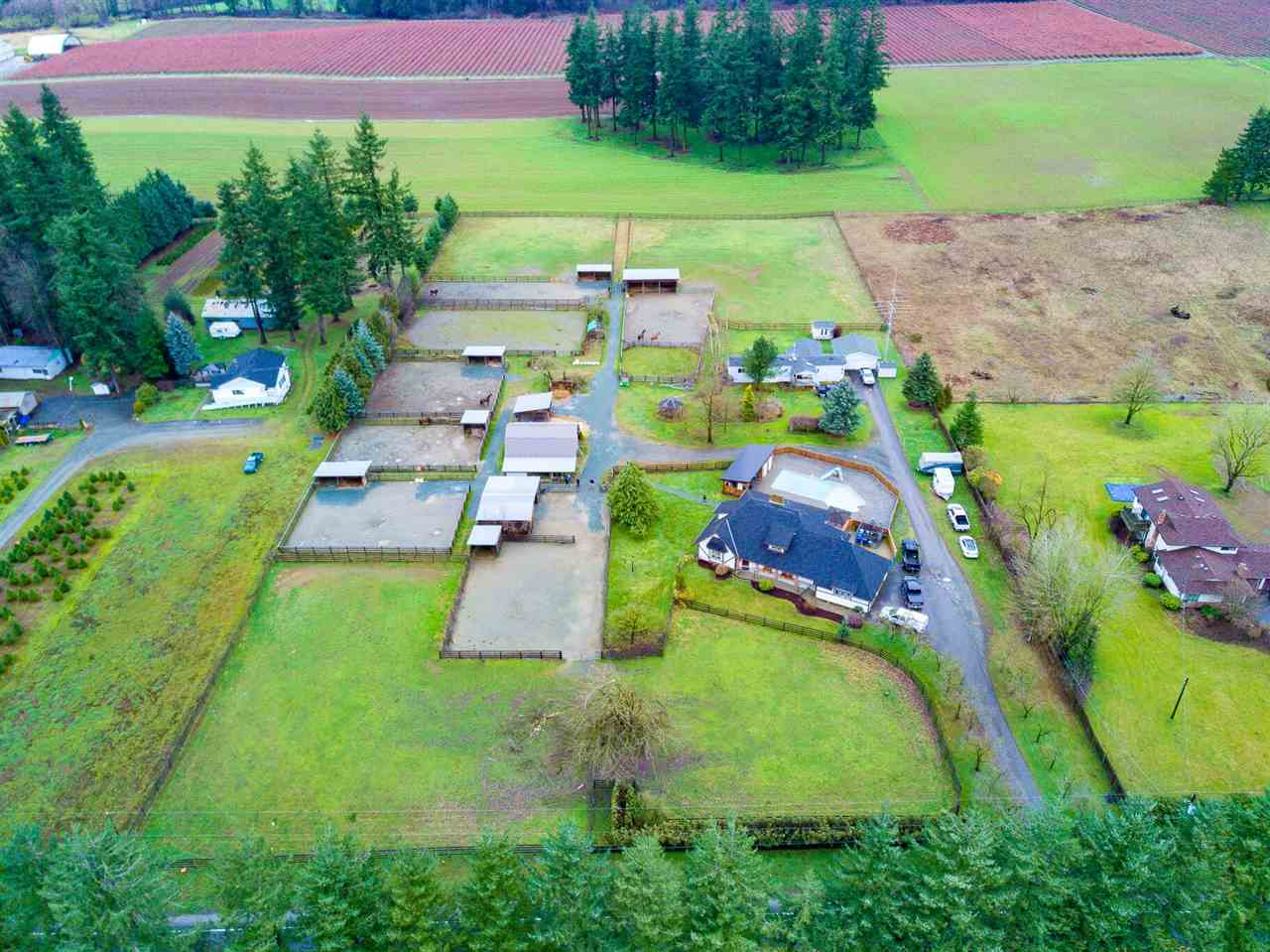 2 FAMILY HOMES EQUESTRIAN SET UP-5 ACRES IN SOUTH LANGLEY WITH MOUNTIAN VIEW-MAIN HOME is 2 storey Tudor style with bsmt over 3100SF, 4 bdrm with many upgrades including kitchen, roof, hot water tank, appliances and paint.Inground pool with new paved decking, 2 fire pits, covered BBQ area with seating and new cedar fence.2 BDRM MOBILE with an addition, garage and private yard.Exceptional horse set up with two barns,6 sand paddocks with shelters and water, 3 grass fields and riding ring. Well established gardens and trees for shade and beauty make this a page out of a country lifestyle magazine you would be proud to call home.The whole property is well drained and gravel walkways and driveways maintained for clean country living.