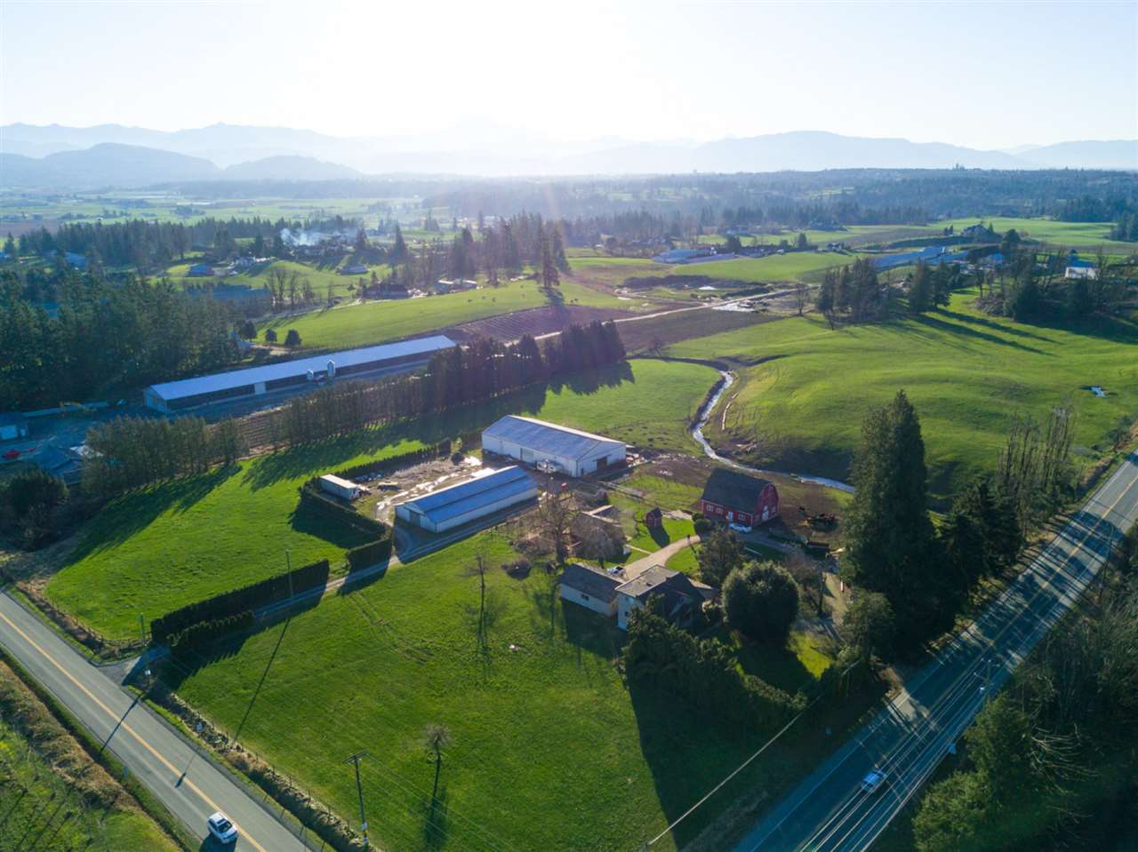 Spectacular Mt Lehman property! 9.15 acres with lush pastures, Mt Baker views, 3000 sq ft family home, a 2nd 3 bdrm home, classic hip roof barn & 13,000 sq ft of shop/storage space. This corner property provides a high visibility location ideal for a business (winery, farm sales...). Primary home is 5 bdrm, 3 bath 2 storey w/ a bsmt & triple garage, updates include new covered deck, plumbing & electrical, new furnace, 2 gas f/p's. 2nd home is a charming 730 sf, 3 bdrm, completely updated. 34' x 40' hip roof barn w/ full loft. 2 quality metal clad shops - 65' x 120' & 50' x 100' (both 200 amp) w/ sep driveway off Harris Rd. 20' x 23' shop/garage. Beaut creek establishes the S property line, so it does not interfere w/ use of prop.