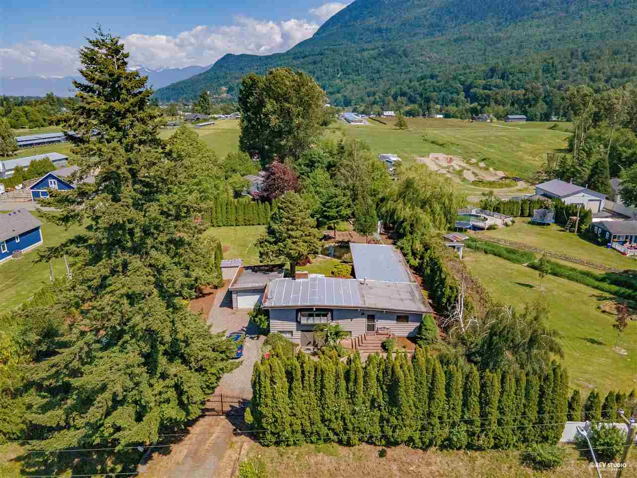 Resort style living on almost 5 acres farm in Yarrow! With stunning landscaping, ponds and complete privacy, the property offers quick access to city centers, hwy 1 and all other amenities while being on a quiet back street. Only 15 min drive to Abbotsford, 10 min drive to Cultus Lake, and Garrison village. This marvelous property has so much to offer. 2 homes, a large barn with 3 horse stalls, a loft, power and water. Main house has 3 bedrooms, each with en suite and a truly GREAT room. Mobile has its own garden, separate driveway, separate septic, above ground pool and has potential for extra rental income.