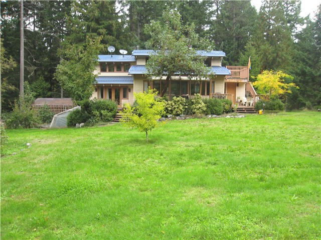 1.7 private, sunny share site features deer-fencing & ornamental garden. Ideal hobby farm with numerous raised beds, fruit trees, chicken coop & 2 greenhouses. 1,300 sq ft sunny, S-facing house features open living/dining/kitchen & bathrm on main flr with window wall & clerestory & generous decks overlooking the garden. A large loft with access to a 2nd flr deck overlooks the living area below. Recent additions include a master suite with custom windows & doors & bath/spa. A 2nd bright bdrm also overlooks the garden. Recent improvements include new lighting, custom kit cupboards, fir flrs & new metal roof. The bsmt has a large workshop & roughed-in sauna. Attached carport & nearby woodshed/garage accommodate 2 vehicles.