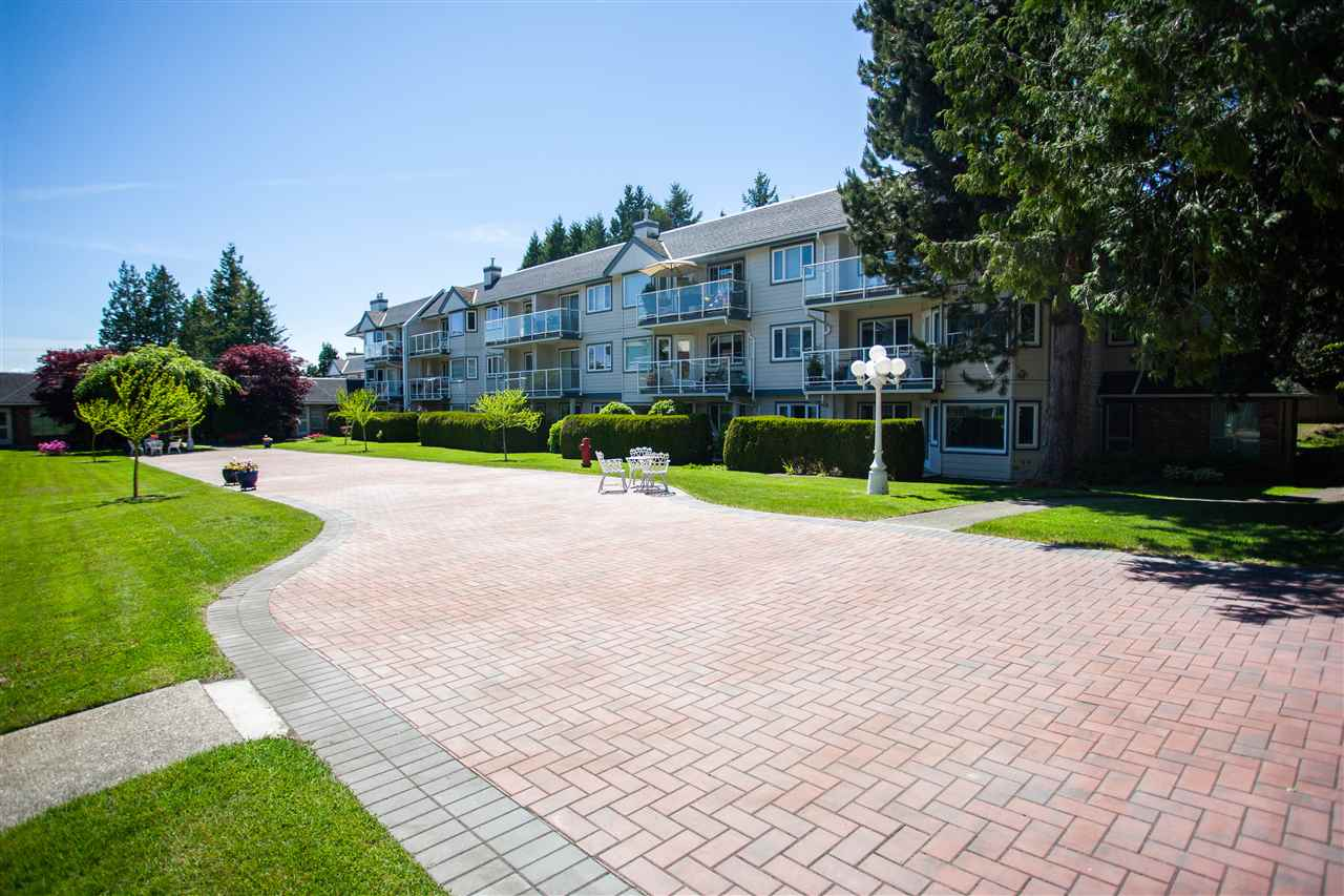 Enjoy the privacy of this ground floor, bright private West exposed corner-end unit. Wheelchair friendly, 50+ adult complex. Boasting the best location overlooking the quiet side of the complex with private patio exposure backing onto lush green treed area. 2 bedrooms + 2 full bathrooms. French doors of the 2nd bedroom can open to the living room with a cozy gas fireplace, enhancing the living area. This condo has been meticulously kept & restored with hardwood kitchen, updated appliances, updated plumbing, updated electrical fixtures. Amenities include common rooftop deck with ocean views, serene gardens, lounge, library & more. Secured parking & locker included. Exterior completely rainscreened. This home is a great option for downsizing to a lovely community. Shop and Compare?