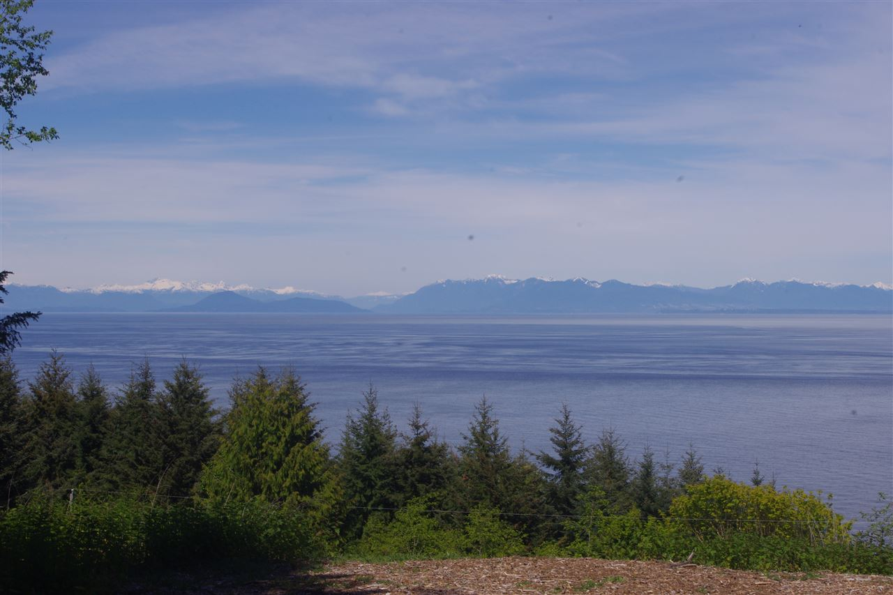 View across the Strait of Georgia from the Vancouver coast line to the Sunshine coast. 5.05 acre treed lot in Panorama Estates with view and potential building site cleared. Lot has driveway roughed in from Panorama Lane (a private access easement). A 5 gallon per minute well. Wet lands and pond. RR zoning allows for the building of a home and cottage. Panorama Estates borders Bodega Ridge Park.
